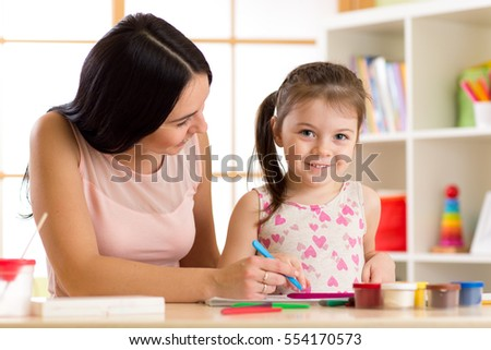 Portrait of happy mother and child daughter painting with pencils