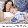 portrait of happy mother and daughter in bed hugging and smiling - stock photo