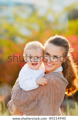 Portrait of happy mother with smiling baby on street