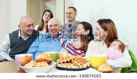 Portrait of happy multigeneration family or group of friends posing together over tea