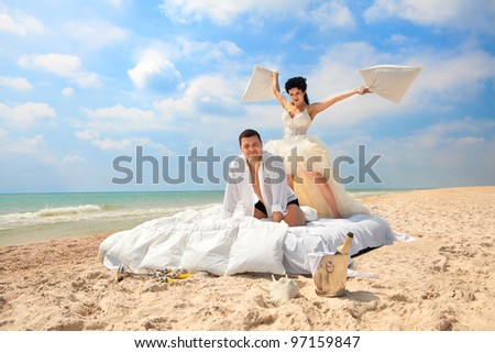 Portrait of happy newlywed couple fighting with pillows in bed on the beach