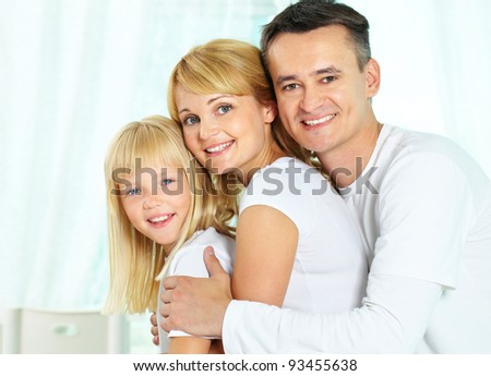 Portrait of happy parents and their daughter looking at camera with smiles
