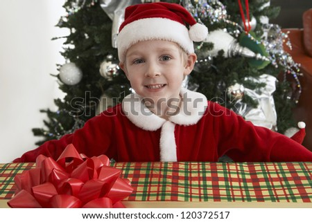 Portrait of happy preadolescent boy in Santa Claus outfit with gift box