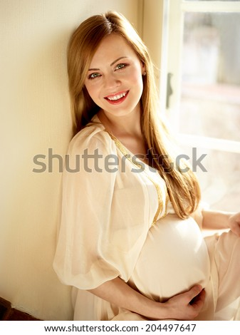Portrait Of Happy Pregnant Woman Sitting Near Window