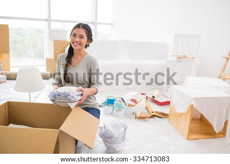 Portrait of happy pretty girl unpacking in her new apartment
