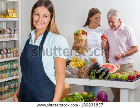 Portrait of happy saleswoman with family shopping in background at supermarket