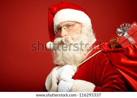 Portrait of happy Santa Claus with big red sack looking at camera