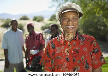 Portrait of happy senior African American woman at golf course with people in background