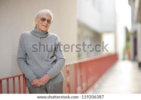Portrait of happy senior woman standing outside building