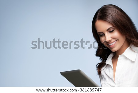 Portrait of happy smiling beautiful young brunette businesswoman using no-name tablet pc, with blank copyspace area for slogan or text message, over grey background