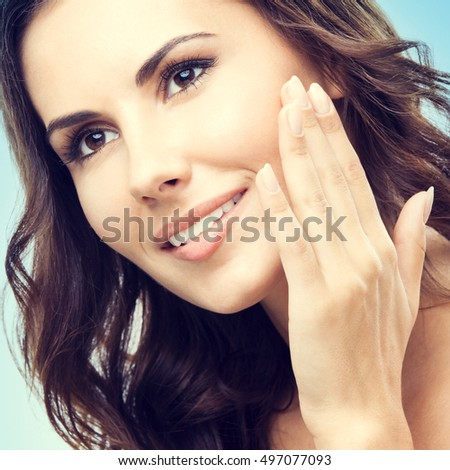 Portrait of happy smiling beautiful young woman touching skin or applying cream, over blue background. Caucasian female model in beauty, healthcare, skincare, face concept. Square composition.