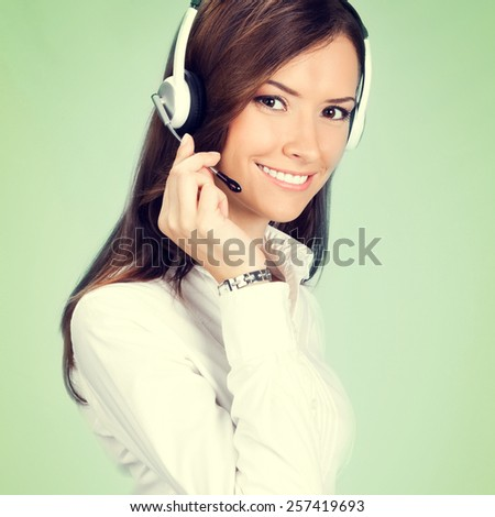 Portrait of happy smiling cheerful customer support phone operator in headset, on green background