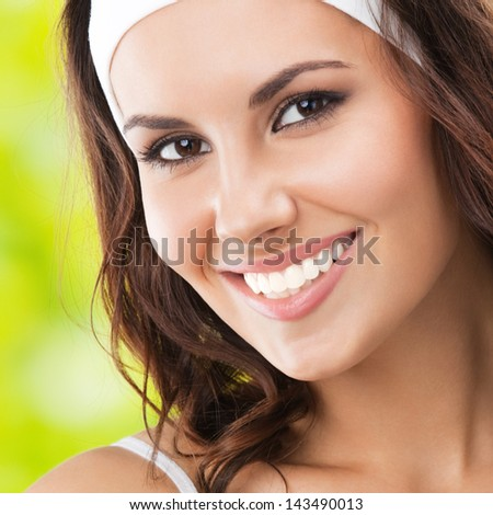 Portrait of happy smiling young beautiful woman in fitness wear, outdoors