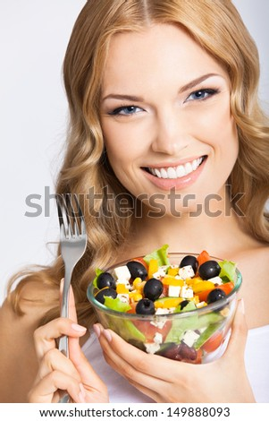 Portrait of happy smiling young beautiful woman with healthy vegetarian salad, over gray background