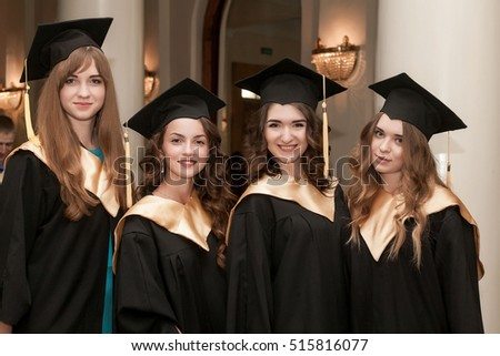 Portrait of happy students in graduation gowns. Happy graduation day.