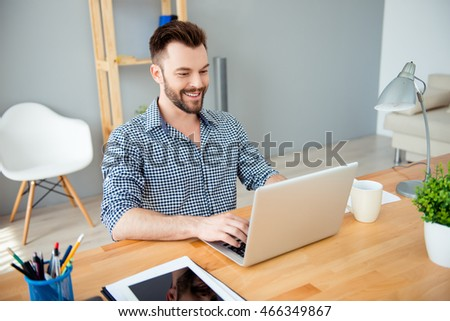 Portrait of happy successful businessman working in office on laptop