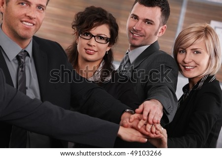 Portrait of happy successful businesspeople joining hands, looking at camera, smiling.