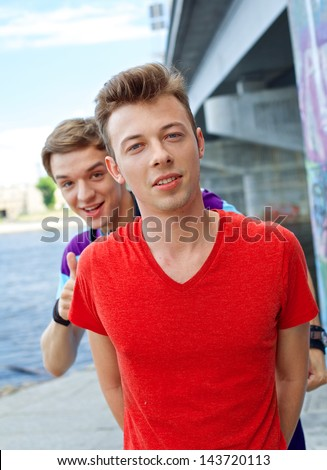 Portrait of happy teens boy with his friend looking at camera. Vertical view