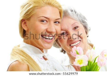 Portrait of happy woman and her senior mother looking at camera