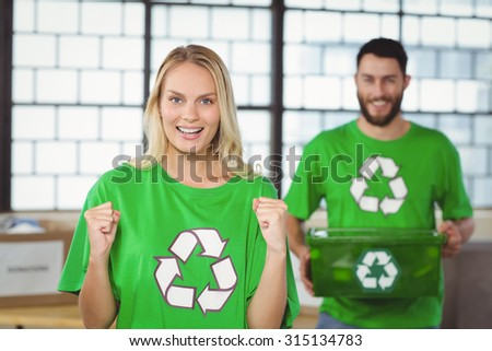 Portrait of happy woman cheering with man in background at office