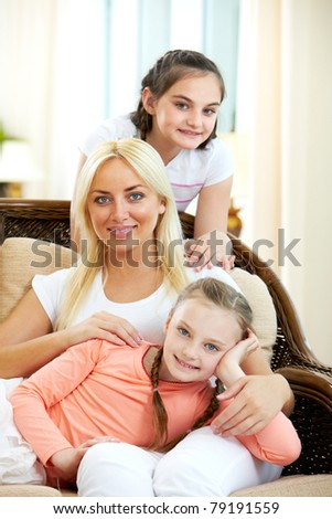 Portrait of happy woman with her daughters sitting on sofa and looking at camera