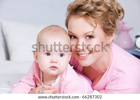 Portrait of happy young attractive mother lying with her baby on the bed at home