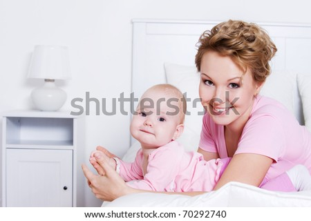 Portrait of happy young beautiful mother lying with her baby on the bed