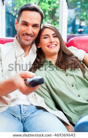 Portrait of happy young couple watching TV. Male and female partners are on sofa. They are sitting at home.
