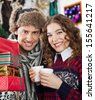 Portrait of happy young couple with presents and coffee at Christmas store - stock photo