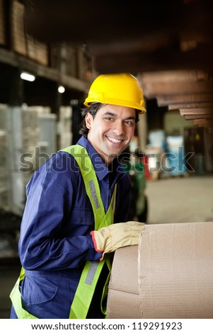 Portrait of happy young foreman in uniform and hardhat working at warehouse