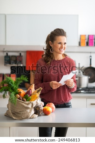 Portrait of happy young housewife holding grocery shopping checks