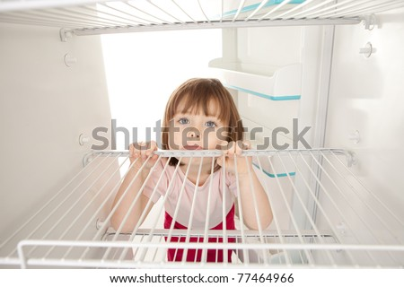 Portrait of happy young preschool girl looking in empty refrigerator.