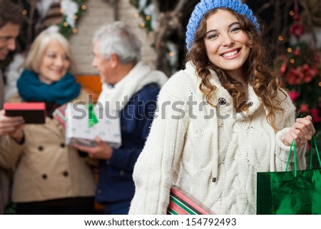Portrait of happy young woman holding in sweater with family standing in background at Christmas store