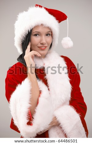 Portrait of happy young woman wearing santa costume, looking at camera, isolated on gray background.?