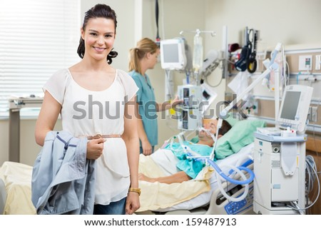 Portrait of happy young woman with nurse examining patient in hospital ...