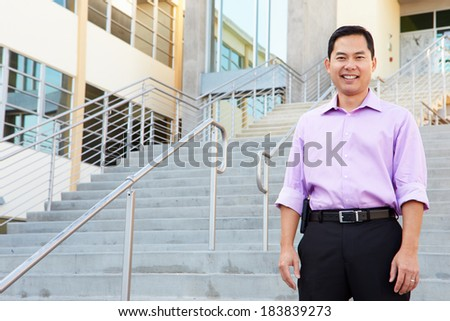 Portrait Of High School Teacher Standing Outside Building