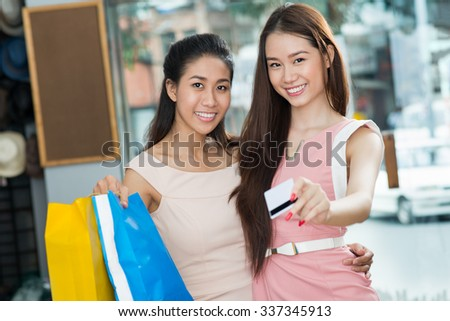 Portrait of hugging Vietnamese girls paying for purchases with credit card