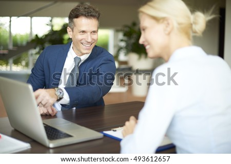 Portrait of investment advisor businesswoman sitting at office in front of computer and consulting with executive professional man.