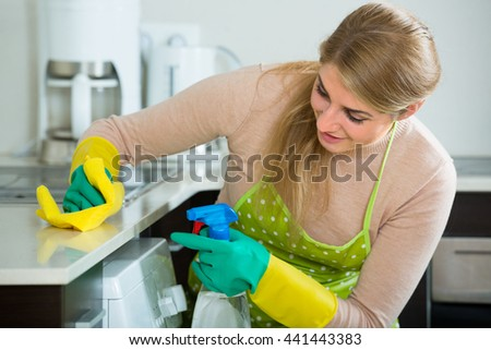 Portrait of joyful female houseworker cleaning in home kitchen