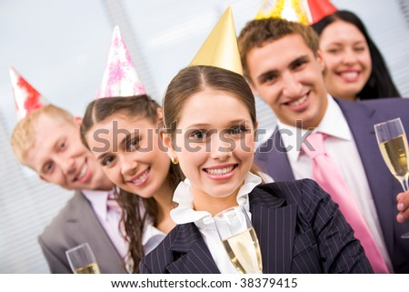 Portrait of joyful female wearing birthday cap looking at camera on background of colleagues