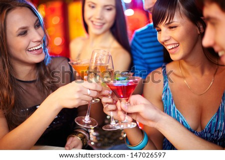 Portrait of joyful friends toasting at birthday party, focus on two happy girls
