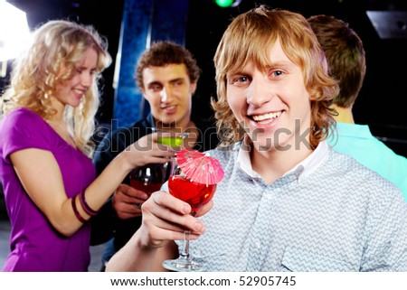 Portrait of joyful guy holding martini glass with cocktail at party