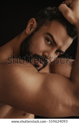 Portrait of Latin handsome shirtless man on black background