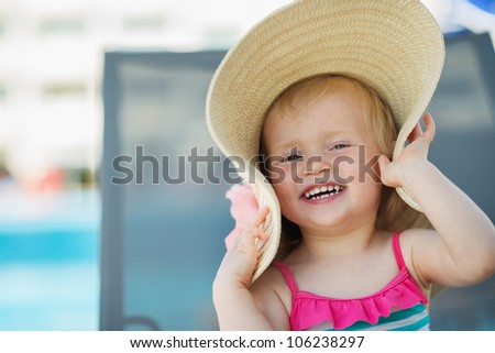 Portrait of laughing baby in beach hat
