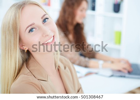Portrait of laughing businesswoman with female colleague on the background. Business and partnership, job offer concept.
