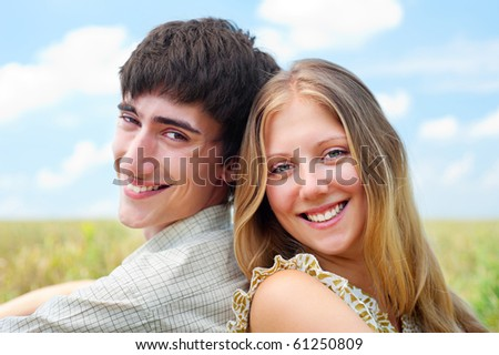 portrait of laughing happy couple over blue sky