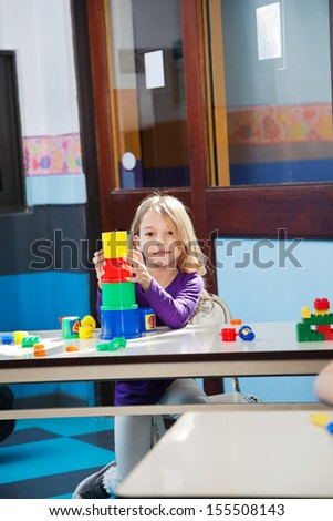 Portrait of little girl playing with toys at desk in kindergarten