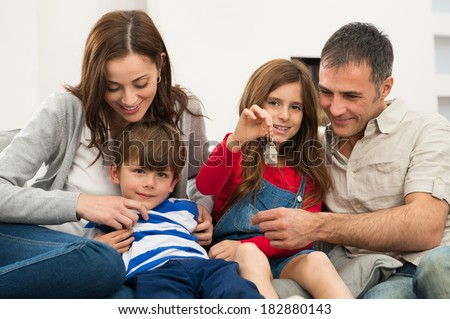 Portrait Of Little Girl Sitting On Couch With Family Showing Key Of New House