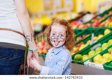 Portrait of little girl sticking out tongue while holding mother's hand in grocery store