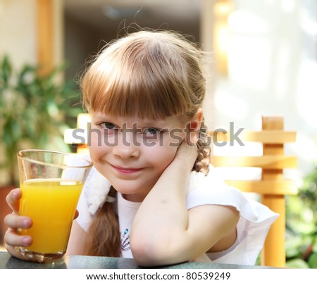 portrait of little girl with orange juice outdoors